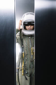 Man posing dressed as an astronaut in skyrocket elevator - DAMF00106