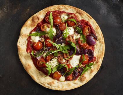 Close-up of pizza with tomatoes, onions, mozzarella and basil - KSWF02107