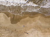 Spain, Sitges, aerial view of mother and daughter lying on sandy beach - PSIF00328