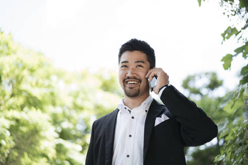Portrait of young businessman talking on the phone outdoors - JPIF00168