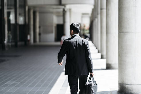Rear view of young businessman walking in the city - JPIF00186