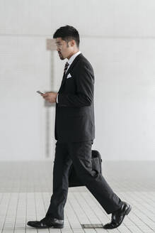 Young businessman with cell phone walking in the city - JPIF00189
