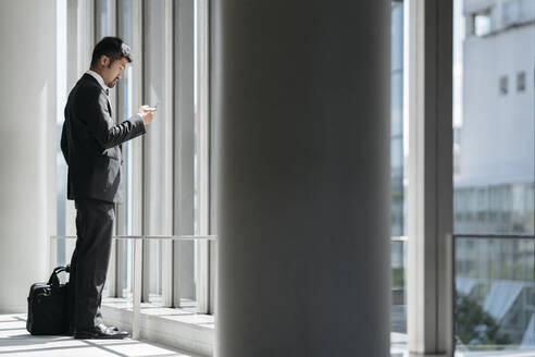Young businessman using cell phone at the window - JPIF00198