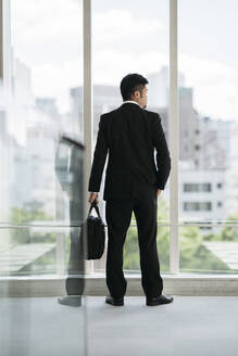 Rear view of young businessman looking out of window - JPIF00204