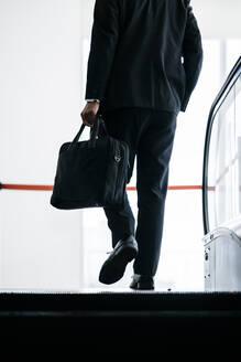 Rear view of businessman on escalator - JPIF00207