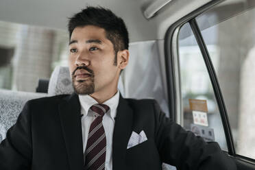Young businessman in a taxi - JPIF00210
