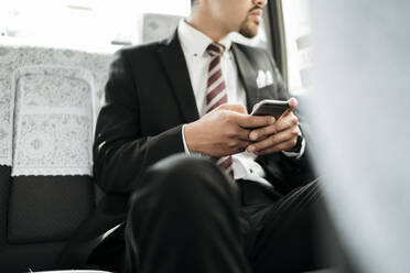 Close-upof young businessman with cell phone in a taxi - JPIF00213