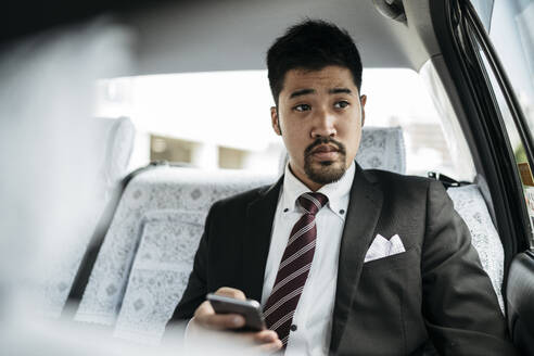 Young businessman with cell phone in a taxi - JPIF00216