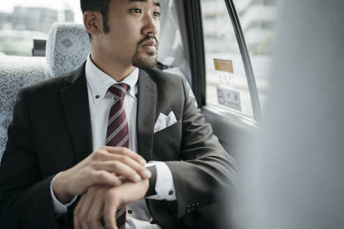 Young businessman in a taxi checking the time and looking out of window - JPIF00219