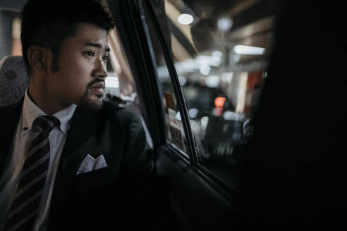 Young businessman in a taxi looking out of window - JPIF00225