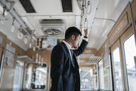Young businessman on a train - JPIF00228