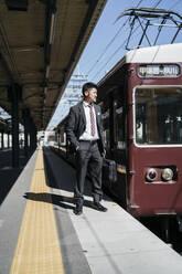 Young businessman on a train platform - JPIF00231