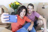 Happy couple taking a selfie in new home - WPEF01924