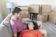 Happy couple relaxing on couch in new home - WPEF01933