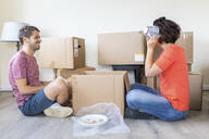 Happy couple moving into new home unpacking cardboard box - WPEF01936