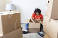 Woman moving into new looking into cardboard box - WPEF01939