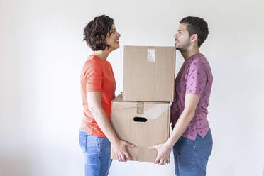 Couple moving into new home carrying cardboard boxes - WPEF01942