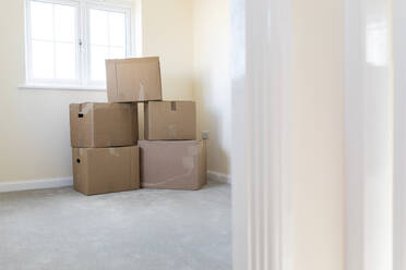 Cardboard boxes in an empty room in a new home - WPEF01945
