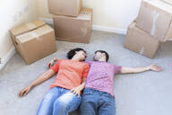Happy couple moving into new home lying on the carpet floor - WPEF01948