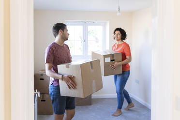 Couple moving into new home carrying cardboard boxes - WPEF01951