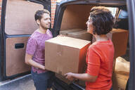 Couple unloading cardboard boxes from van - WPEF01960