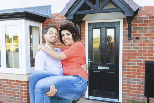 Happy man carrying woman in front of their new home - WPEF01963