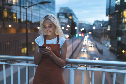Young woman in the city at dusk looking at her smartphone - WPEF01969