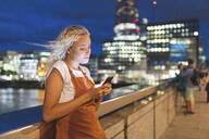 Young woman in the city at dusk looking at her smartphone - WPEF01981