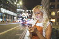 Young woman in London at night looking at her smartphone - WPEF01990