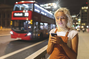 Young woman in London at night looking at her smartphone - WPEF01993