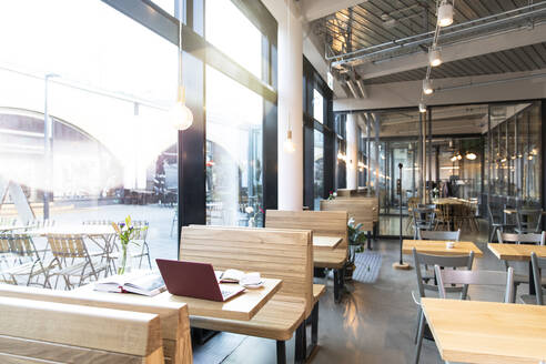 Laptop and books on table in a modern cafe - FKF03618