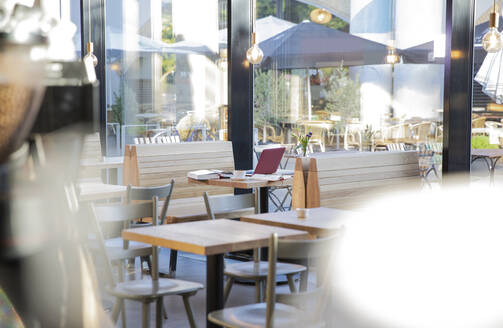 Laptop and books on table at a modern cafe - FKF03624