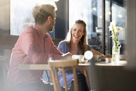 Laughing woman and man talking at table in a cafe - FKF03630