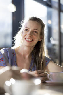 Porrait of smiling woman in a cafe - FKF03633