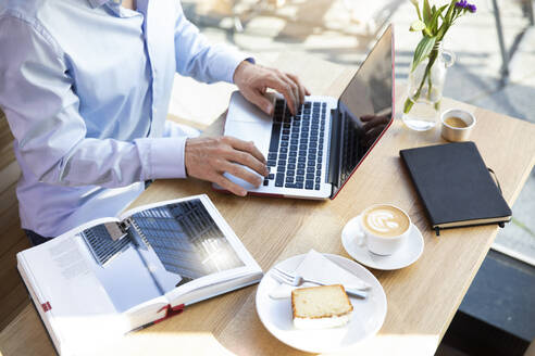 Close-up of man using laptop in a cafe with book on table - FKF03642