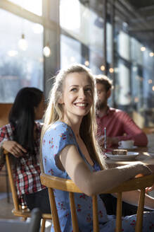 Portrait of smiling woman with friends in a cafe - FKF03645
