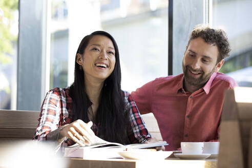 Happy man and woman with book in a cafe - FKF03651