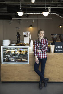 Woman standing at the counter of a cafe looking around - FKF03654