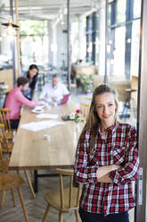 Portrait of casual businesswoman in a cafe with colleagues having a meeting in background - FKF03678