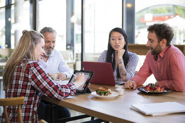Casual business people having a meeting in a cafe - FKF03687