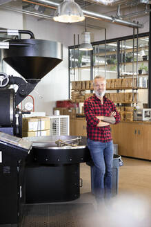 Portrait of confident mature man in a coffee roastery - FKF03696
