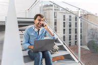 Casual businessman sitting on stairs with laptop talking on the phone - AFVF03984