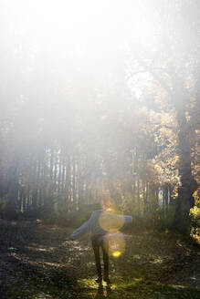 Woman relaxing in autumn forest - DAMF00110