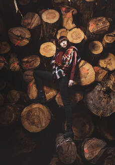 Portrait of young woman at stack of wood - DAMF00116