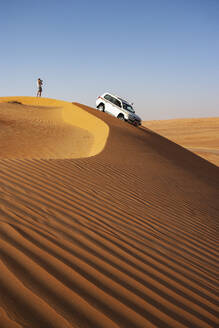 Man with off-road vehicle, taking pictures in the desert, Wahiba Sands, Oman - WWF05283