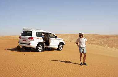 Tourist standing in the desert next to off-road vehicle, Wahiba Sands, Oman - WWF05286