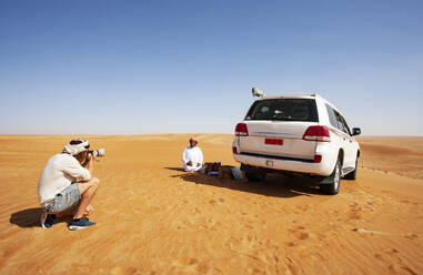 Tourist taking pictures of his local driver in the desert, Wahiba Sands, Oman - WWF05289