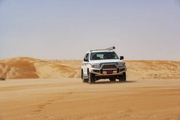 Tourist driving in desrt in off-road vehicle, Wahiba Sands, Oman - WWF05292