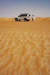 Tourist talking to his driver in the desert next to off-road vehicle, Wahiba Sands, Oman - WWF05295