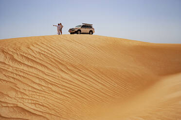 Tourist standing on dune next to off-road vehicle with his driver, Wahiba Sands, Oman - WWF05298